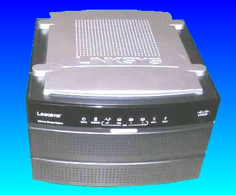 This photo was taken from the top of the Linksys NAS200. The unit has a silver top and dark grey base with status leds on the front. It shows positions for 2 hard drives.