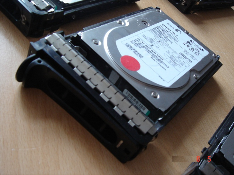 A Hard Drive taken from a Dell Server shown in it's caddy. The drives are 3.5inch and 146gb each. The drives are lockable and have a red dot on the case. To the edge of the photo you can see the other drives from the array.