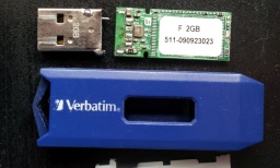 A Verbatim USB memory stick broken apart to show its internal circuit board. The silver usb connector is shown broken off the end and solder pads ripped off the pcb
